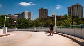 Sirva caminar abajo de una rampa del parking, mirando highrises adentro Foto de archivo