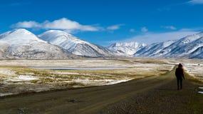 Sirva caminar en el camino entre las montañas nevosas Fotografía de archivo libre de regalías