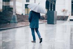 Sirva caminar en la ciudad con el paraguas en día lluvioso imagenes de archivo