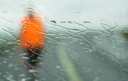 Sirva caminar en la lluvia con la chaqueta fluorescente Imágenes de archivo libres de regalías