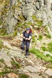 Sirva caminar en rastro de montaña difícil con el cable de la ejecución Imagen de archivo libre de regalías