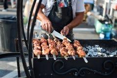Sirva cocinar, sólo las manos, él están cortando la carne o el filete para un plato Parrilla deliciosa Fin de semana de la barbac imagen de archivo libre de regalías