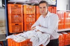 Sirva con la cesta de ropa que se coloca en lavadero Fotos de archivo libres de regalías