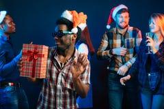 Sirva con la sonrisa encantadora que celebra el regalo de la Navidad en manos Foto de archivo