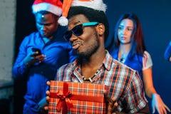 Sirva con la sonrisa encantadora que celebra el regalo de la Navidad en manos Imagen de archivo
