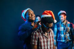 Sirva con la sonrisa encantadora que celebra el regalo de la Navidad en manos Foto de archivo libre de regalías