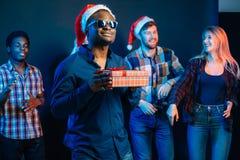 Sirva con la sonrisa encantadora que celebra el regalo de la Navidad en manos Imágenes de archivo libres de regalías