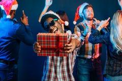 Sirva con la sonrisa encantadora que celebra el regalo de la Navidad en manos Fotos de archivo libres de regalías