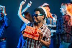 Sirva con la sonrisa encantadora que celebra el regalo de la Navidad en manos Imagen de archivo libre de regalías