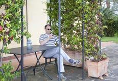 Sirva controlar su teléfono móvil en una terraza Foto de archivo