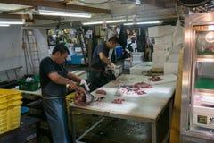 Sirva cortar un pescado en el mercado de pescados de Tokio Foto de archivo