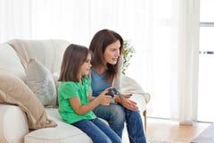Sirva de madre a animar a su hija que juega al juego video Imagen de archivo