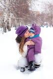 Sirva de madre a besar y a detener a un bebé, invierno Fotos de archivo
