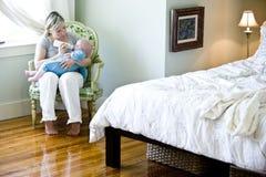 Sirva de madre a criar con biberón al bebé en dormitorio Fotografía de archivo libre de regalías