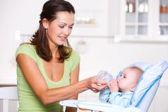 Sirva de madre a dar el agua al bebé Imagen de archivo libre de regalías