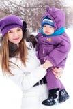 Sirva de madre a detener a un bebé, nieve, parque del invierno Imagenes de archivo