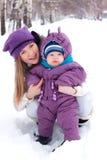 Sirva de madre a detener a un bebé, nieve, parque del invierno, caminata Fotografía de archivo libre de regalías