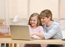 Sirva de madre a explicación a la hija sobre usar una computadora portátil Imagen de archivo libre de regalías