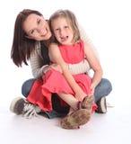 Sirva de madre a la diversión y a la risa de la hija que se sientan en suelo Imagenes de archivo