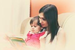 Sirva de madre a leer un libro con su peque?a hija imagen de archivo