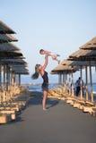 Sirva de madre a los juegos con su niño en la playa Foto de archivo libre de regalías
