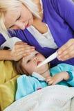 Sirva de madre a tomar su temperatura de la hija Fotografía de archivo