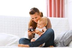 Sirva de madre y bebé sonriente que mira las fotos en cámara Fotos de archivo libres de regalías