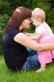 Sirva de madre y su bebé en jardín Imagen de archivo libre de regalías