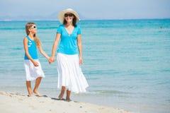 Sirva de madre y su hija vestida en blanco y azul divirtiéndose en la playa Imagen de archivo libre de regalías