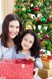 Sirva de madre y sus regalos de la Navidad de la apertura de la muchacha Fotografía de archivo