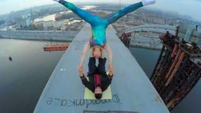 Sirva detener a la mujer encima del puente, yoga acrobática en la gran altura, adrenalina metrajes