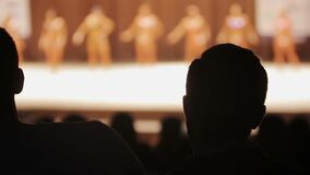 Sirva disfrutar de la competencia femenina del levantamiento de pesas, espectador masculino contento, tiempo libre metrajes