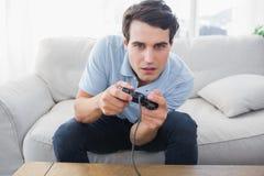 Sirva divertirse con los videojuegos mientras que lo sientan en un sofá fotografía de archivo