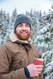Sirva el árbol de navidad cerca adornado de consumición del café en bosque del invierno Imagen de archivo libre de regalías