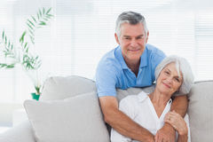 Sirva el abarcamiento de la esposa que se está sentando en el sofá Imagenes de archivo