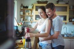 Sirva el abarcamiento de la mujer de detrás mientras que prepara el smoothie de la sandía en la cocina Fotos de archivo