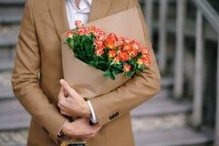 Sirva el abarcamiento de un ramo de flores, doblado en papel del arte Fotos de archivo libres de regalías