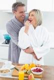 Sirva el abarcamiento de una mujer de detrás en cocina Foto de archivo libre de regalías