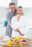 Sirva el abarcamiento de una mujer feliz de detrás en cocina Foto de archivo libre de regalías