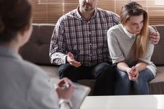 Sirva el abrazo de su esposa y hablar con un terapeuta de los pares imagen de archivo