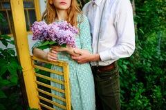 Sirva el abrazo de su novia que esté sosteniendo un ramo de lilas fotos de archivo