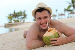 Sirva el agua fresca de consumición del coco en la playa Foto de archivo