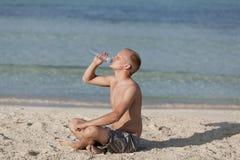 Sirva el agua potable de una botella en el retrato de la playa foto de archivo