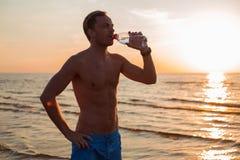 Sirva el agua potable después de su entrenamiento en la playa imagenes de archivo