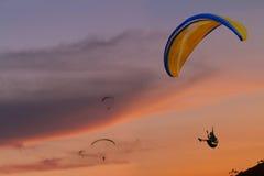 Sirva el ala flexible del vuelo en la puesta del sol con el fondo anaranjado foto de archivo