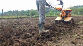 Sirva el arado del campo con el cultivador, preparación del jardín almacen de metraje de vídeo