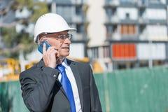 Sirva el architector al aire libre en el área de la construcción que tiene conversación móvil Foto de archivo libre de regalías