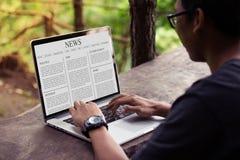 Sirva el artículo de noticias de la lectura sobre el ordenador portátil/la pantalla de ordenador foto de archivo libre de regalías