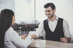 Sirva el barista que da la taza de café al cliente en el café Imagen de archivo