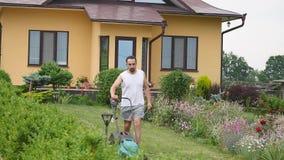 Sirva el césped de siega del jardín con la máquina del cortacéspedes en yarda almacen de metraje de vídeo